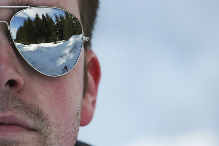 Man wearing sunglasses to block glare from snow