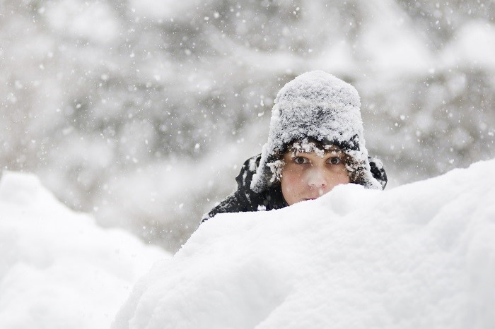 Teen hiding behind snowbank