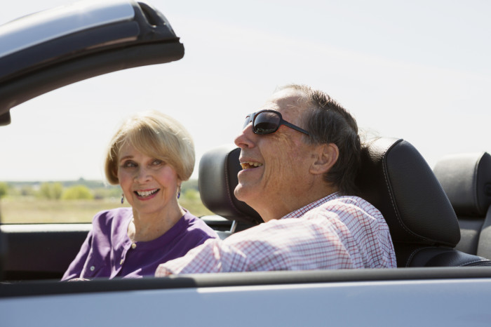 Senior couple enjoying a road trip in a convertible.